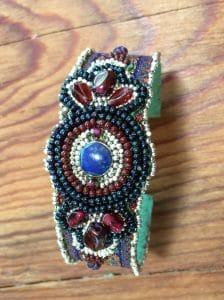 This is a bead embroidery cuff with garnets.