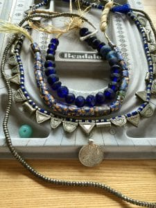 The telsem boxes are charms in this three-strand treasure necklace for MaryEllenBeads.