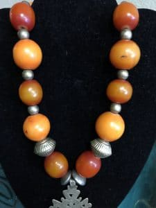 This is a simple treasure necklace with amber, silver and a focal cross.