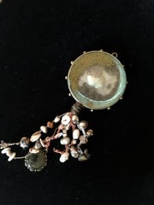 Sand dollar halo is a piece of resin jewelry created by Mary Ellen Beads Albuquerque.