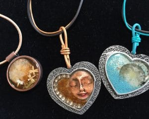 These leather jewelry and ice resin jewelry bezels show sand dollars and faces by Mary Ellen Beads Albuquerque.