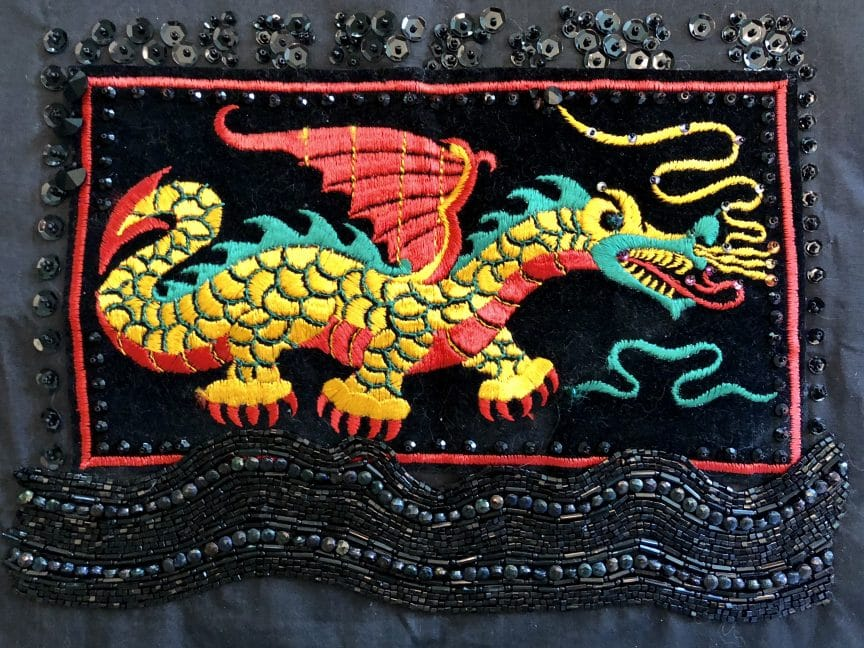This slow stitch dragon contains both embellishments and symbology.
